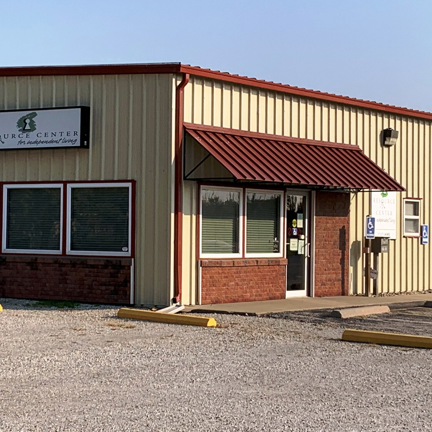 Tan colored office building with dark red trim and awning