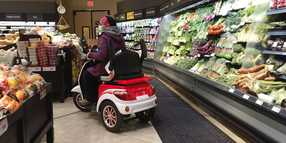 disabled woman shopping for groceries on scooter